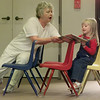 """10/11/99---Bailee Hopkins, 3, reads a book with her grandmother, Dr. Fran Hopkins, Monday while seated in """"airplane seeting"""" at Longview Public Library. Bailee had rearranged the chairs to resemble an airplane so they could pretend they were in flight while reading. bahram mark sobhani"""