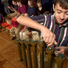 "Alex Frenkel, 11, adds another candle to the Menorah as he and other students at the Temple Emanu-El Religious School rehearse for their Hanukkah performance of ""Who Wants To Be A Maccabee?"" Thursday December 21, 2000, Les Hassell"