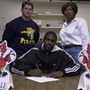 12-21-00---Former Pine Tree Pirate Chris Johnson, center, prepares to sign on with the Louisville Cardinals for a football scholarship.  Present to congratulate his signing were Pine Tree Head Coach Terry Waldrep and Chris' sister Jennifer Johnson.  Brian Jenkins
