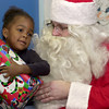 Decherne Braggs, 3, hugs her Christmas present from Santa Claus Thursday December 21, 2000 during a visit to the Longview Child Development Center. Les Hassell