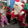 Santa and his elves lean in close to hear what it is that three year old Francisca Brooks wants for Christmas Thursday December 21, 2000 during a visit to the Longview Child Development Center. Les Hassell