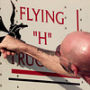 2/29/00---Mac McNaughton, dipatch manager, affixes a logo to one of Henderson Trucking's rigs. bahram mark sobhani