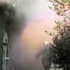 2-29-00---A Longview Firefighter walks to the front of a house while flames jump out from the side of the house while burning Tuesday afternoon on idelwood Dr. in Longveiw. Kevin Green