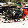Andy Newton,8, holds Joshua Parkhurst,9,  feet up so they can slide down a neighbors yard Saturday afternoon.  by DARLENE-1-29-00