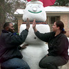 1-28-00---George Jones, left, and Shree Anderson, right, give each other a hi five Friday afternoon in front of the six foot tall ice man they constructed yesterday afternoon during the sleet storm in the 1100 BLK. South 13th St. in Longview. Kevin Green