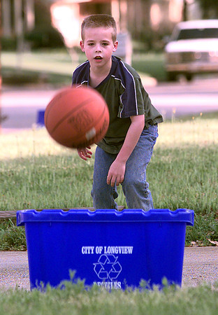 3-30-00---Todd McDonald, the 9 year old son of Rick and Terri McDonald, watches his basketball as he shoots hoops into the recycling bin Thursday afternoon in the 1800 BLK. of Swan in Longview.Kevin GReen