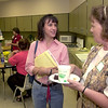 8-13-01----Longview High School teacher Karen Bennett, left, and first year teacher Debi Conrad, right, visit during a reception for new faculty at the high school Monday afternoon in Longview. Kevin Green