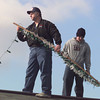 Kelly Allen, left, and son Zack take to their north Longview  roof top Monday afternoon to collect christmas lights for storage until next year.  by DARLENE-1-31-01