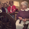 Margaret Mintor answers questions from Lainie Bagley,left, Caitlin Gilchrist, and Sherry Bagley as she works the spinning wheel.  Mintor was one of the actors participating in the Living History Christmas at Gregg County Historical Museum Saturday morning.  by DARLENE-11-31-01