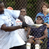 Ron Shepherd hits a homerun Saturday at a softball tournament to raise money for a new wheelchair for Jonathan Pierce, 14, right,While Pierce's mother, Shanequa Writt, center, and his nurse, Karen Lair, far right, look on. Saturday August 31,2002. Ricardo B.Brazziell