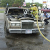 7-7-02 ------ Longview firefighter Chris McGinnis (left) puts out a fire in a 1986 Lincoln Towncar while firefighter Jerry Taylor (right) fills out an accident report in the parking lot of Autozone on Hwy 80 near Spur 63.  The car's owner, Allen Smith Jr., was driving on Highway 80 when he noticed smoke coming from under the car's hood, and pulled over into the parking lot and got out of the car just before flames engulfed the passenger compartment.  JUSTIN BAKER