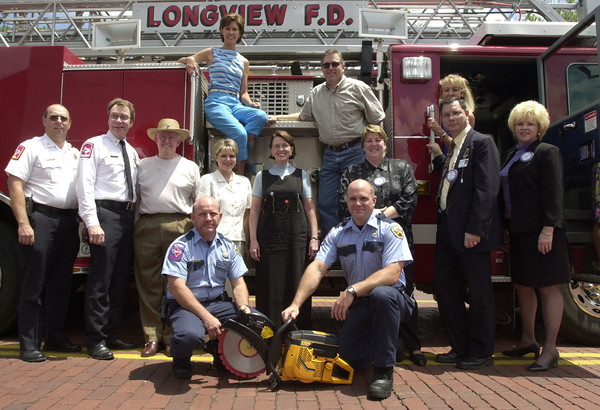 Longview Firefighters Hilton Jay,left, and Mark Baker kneel beside the K-12 rescue saw as LFD Thomas Mock and Fire Chief Richard Lazarus stands with members of the Greggton Rotary Club in front of the Summit II. The organization donated the $1,000. plus saw before the start of their monthly luncheon.  by DARLENE-5-31-02