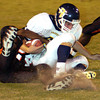 Pine Tree's #6 gets drug to the ground by Gilmer's #24 during Friday's September 27, 2002 game in Gilmer. Les Hassell