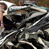 A state Trooper checks out the mangled remains of a car involved in an accident of Hwy 31 Wednesday, December 31. 2003. (Les Hassell/News-Journal Photo)