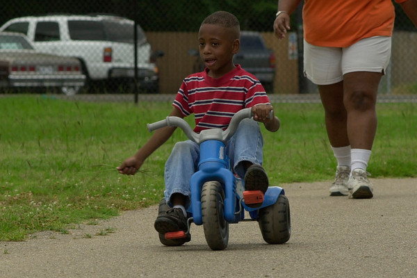 Five year-old Justin Buccanan  pedals ahead of his mother, Verdell Buccanan as the two enjoy laps around the walking path at South Ward Neighborhood Park Monday morning.  by DARLENE-6-30-03