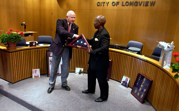 Police Chief A.J. Key presents retiring deputy chief Darcy Burton with a flag during a retirement party Monday March 31, 2003. Les Hassell