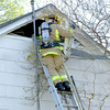 11-30-2003 --- A firefighter pulls apart a vent to get into the attic while battling an electrical fire in a home on Travis Ave. in Longview Sunday morning. No one was injured, and the fire was quickly put out before it could spread beyond the attic.  JUSTIN BAKER
