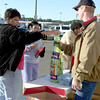 11-28-2003 --- Jackie Mays and her daughter Aaliyah, age 9, put their Toys for Tots donations in a bottle held by Paul Dillon at WalMart Supercenter in Longview on Friday afternoon.  JUSTIN BAKER
