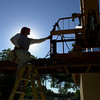 Juan Vagquez of William Construction is silhouetted by the sun as he climbs a ladder to work on roof  Monday September 29,2003. Ricardo B.Brazziell