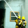 Firefighters spray water on the eaves of a burning house on Birdsong Wednesday evening, June 30, 2004.  JUSTIN BAKER