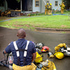 A Longview firefighter takes a break as fellow firefighters douse the final embers of a house fire that destroyed a home on Birdsong Wednesday, June 30, 2004. (Les Hassell/News-Journal Photo)