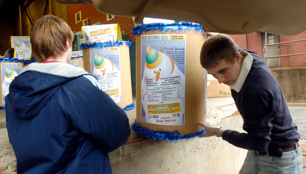 Longview News-Journal employees Patric McGaughey, left, and Jason Tyner, right, load food drive barrel fro delivery Tuesday November 30, 2004 at the paper in Longview. Kevin Green