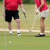 Robin Glass, right, watches her putt, along with Tom Suess, left, from the 9th hole as she plays with her dad Ron Glass' clubs during the American Heart Association's Ron Glass Memorial golf tournament Friday, April 29, 2005 at Pinecrest Country Club in Longview.  (Kevin Green/News-Journal Photo)