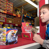 Holden Cathey eyes the fireworks for sale at the Fantastic Fireworks stand on Highway 289 Friday night.  His father, John Cathey who bought fireworks to shoot off with his sons on New Year's Eve, said that local burn bans will not affect their festivities this year, because a ban has not been issued for Harrison County where they live. (Luisa Morenilla/News-Journal Photo.)
