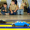 Cub Scouts watch as pinewood racers streak by Saturday, January 29, 2005. (Les Hassell/News-Journal Photo)