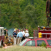 Emergency services personel gather next to an oil well pump jack as another well burns Thursday, July 28, 2005 off Texas FM 1845 in Gregg County.  (Kevin Green/News-Journal Photo)