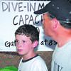 Trevor Jacobus(left) listens to his dad Jake Jacobus(right) (both from longview while wating in line to see the movie on Saturday, July 30, 2005 at The Longview Swim Center in Longview. (Courtney Case/News-Journal Photo)