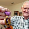 Ray Smith holds a purple heart medal he was awarded in 1945, Tuesday, June 28, 2005 at his home in Kilgore. (Kevin Green/News-Journal Photo)