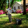 "With azeleas in bloom, Henry Clark Gay takes advantage of the wonderful weather and rakes leaves in his front yard in south Longview Wednesday, March 30, 2005. ""There's a special way to rake these leaves; I've been doing it for 12 years and I've just about figured it out."" (Les Hassell/News-Journal Photo)"