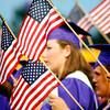 Small American flags form a frame around Hallsville senior Sarah Ann Dulis(center) from Hallsville during the Hallsville High School Graduation at Bobcat Stadium in Hallsville.(Courtney Case/News-Journal Photo)