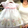 Jessica Kaufman, an employee at Hopscotch in downtown Longview, displays an Easter dress that is among the more popular Easter dresses they are selling this year. (Luisa Morenilla/Longview News-Journal)
