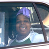A suspect arrested after a police chase sits in the patrol and smiles for the camera as she was photographed  by newspaper and television cameras Monday, February 27, 2006 along I-20 in Liberty City. (Kevin Green/News-Journal Photo)