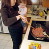 Melinda Dunn, left, browns hamburger meat while holding her 22 month old daughter Rebecca Dunn Tuesday, February 28, 2006 at her home in Longview.  (Kevin Green/News-Journal Photo)