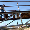 """Robert Buchanan, who is staying in the Ramanda Inn crosses the pedestrian bridge next to Town Lake Plaza off Spur 63 Tuesday, January 31, 2006 in Longview. Robert said """"he was a conductor on a railroad and he walks alot so if he can take a short cut he trys."""" (Kevin Green/News-Journal Photo)"""