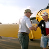 Brian Porsch of Lucas, Texas, right, thanks pilot Roscoe Armstrong for the ride in a World War II airplane at the Great Texas Balloon Race, just after landing, Saturday, July 15, 2006.  He and three others won the opportunity to ride in the airplanes through a raffle. (Luisa Morenilla/Longview News-Journal)