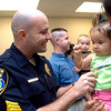 Bob Kemper accepts congratulations from friend Airiam Howell and her daughter Rainey, 1, after being promoted to sergeant at a ceremony at the Roy Stone Police Training Center on Tuesday, September 5, 2006.  (Luisa Morenilla/Longview News-Journal)