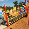 Jennifer Puckett of Longview brings her son Dane Puckett up the ramp; the ramp stops at a point leading up to the slide, on The Neal McCoy Playground on Thursday, October 20, 2005 at Neal McCoy's Playground in Spring Hill. (Courtney Case/News-Journal Photo)