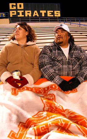 Pat and David Gomez bundeled up Wednesday night to watch their son Zachery play in the Pine Tree Alumni soccer game at Pine Tree Stadium. (Jacob Croft Botter/News-Journal Photo)