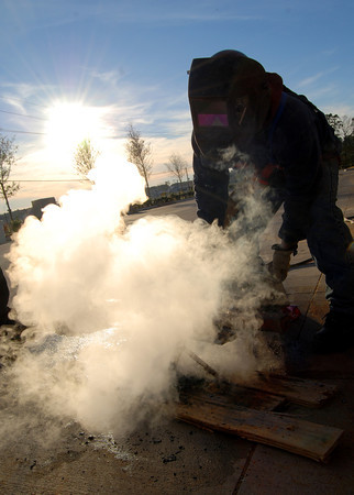 Armondo Quinto pours some water onto some hot metal that produces a cloud of steam in the cold weather that moved into Longview yesterday evening. (Jacob Croft Botter/News-Journal Photo)