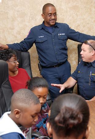Byron Mills, center, listens as Fire Marshall Mark Moore tells a story about him to his wife Carlette, as there children enjoys some cake and punch at a reception marking his retirement on Wednesday at the Central Fire Station in Longview. (Jacob Croft Botter/News-Journal Photo)