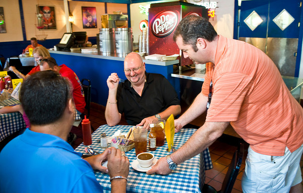 Dudley's Cajun Cafe manager Jake Scherrer Waits on Gene Branch and Keith Gray of Houston Tuesday, August 31, 2010 during the Too Hot to Cook fundraiser. (Les Hassell/News-Journal Photo)