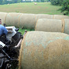 Alan Branham sits atop a tractor in the hay storage area as freshly baled hay is in the hay meadow Wednesday, June 30, 2010 off Northridge Road in Gregg County.  (Kevin Green/News-Journal Photo)