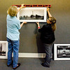 Nina Kennedy and Tammy Cromer-Campbell hang historical photos of Gregg County in preparation for tonight's Art Walk at the Gregg County Historical Museum. Some 15 downtown museums, retail shops and restaurants will remain open until 8 p.m. today to welcome downtown strollers in the quarterly event. Musicians typically perform in several nooks during Art Walk, or on the downtown sidewalks. Participating venues will host works of more than 30 local and regional artists in media including watercolor, oil painting, acrylic, ceramic, photography, and glasswork. (Michael Cavazos/News-Journal Photo)