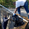 Jimmy Johnson holds a bag as Randy Butler picks up some trash Sunday in Kilgore. (Justin Baker/News-Journal Photo)