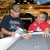 Kevin Baxter looks at a brochure while Terry Barnson of Nichols Marine tells him about the features of a boat Sunday at the 29th Annual Boat, RV and Camping Expo at Maude Cobb Convention and Activity Center. (Justin Baker/News-Journal Photo)