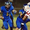 Carlisle's Mikey Henderson runs the ball as teammate Chris Mendoza blocks Dallas First Baptist defender Matt Ackley during a game Friday, September 30, at Carlisle. (Justin Baker/News-Journal Photo)